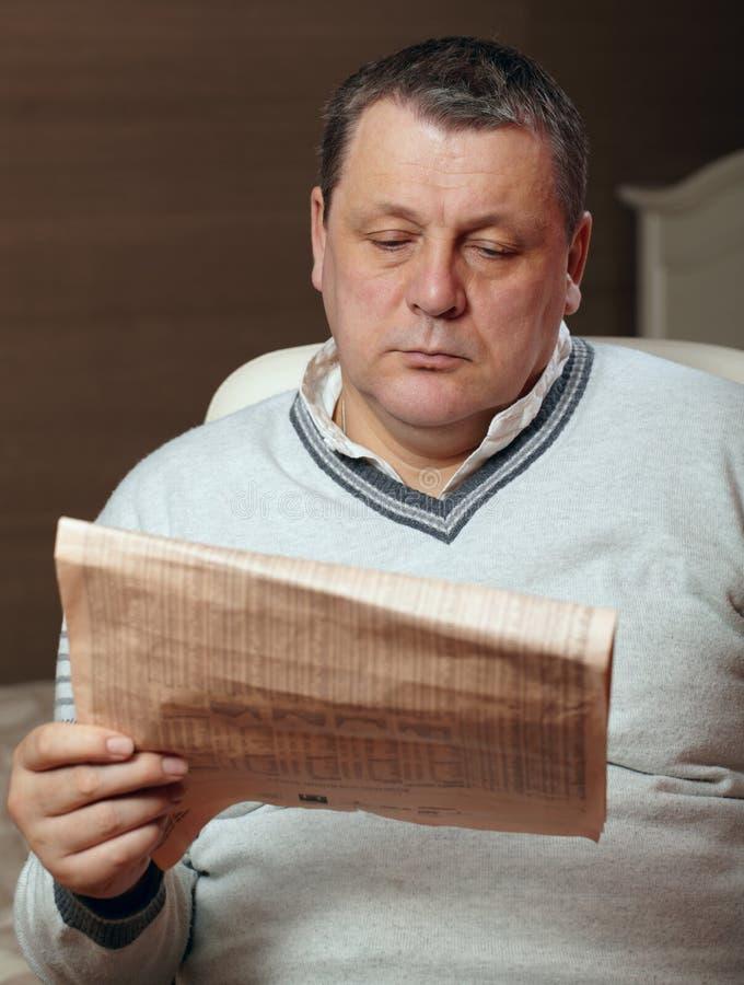 Portret van de hogere krant van de mensenlezing thuis. royalty-vrije stock afbeelding