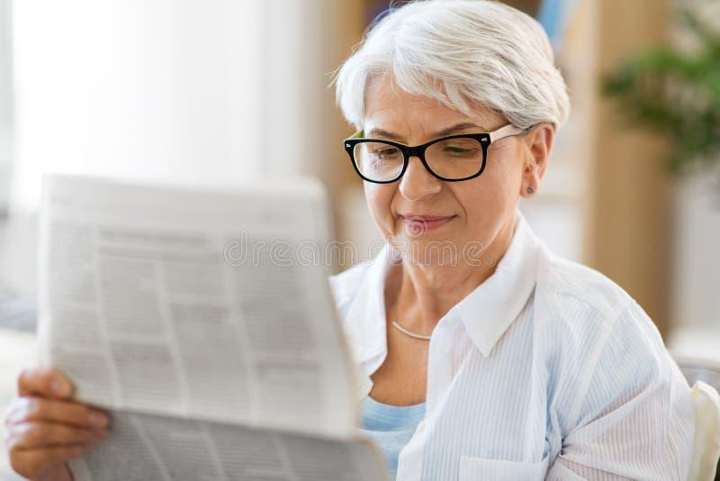 Portret van de hogere krant van de vrouwenlezing thuis royalty-vrije stock foto