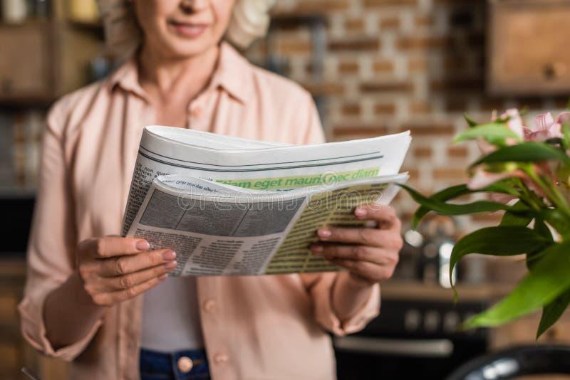 Portret van de hogere krant van de vrouwenlezing tijdens ontbijt royalty-vrije stock afbeelding