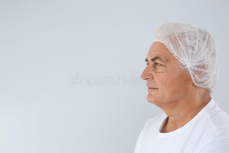 Portret van de hogere mens met tekens op gezicht die voor kosmetische chirurgie tegen witte achtergrond voorbereidingen treffen stock foto's