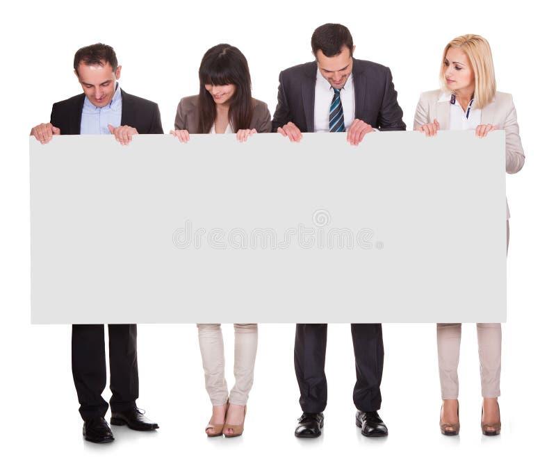 Portret van de holdingsaanplakbiljet van de zakenluigroep stock foto's