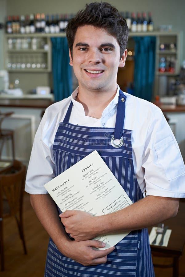 Portret van de Holdingsmenu van Chef-kokstanding in restaurant stock afbeelding