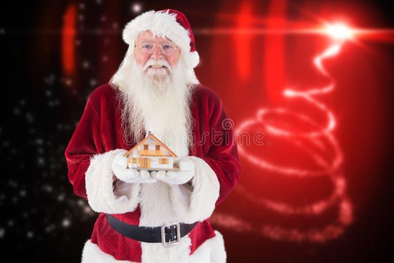 Portret van de holdingsstuk speelgoed van de Kerstman huis stock foto's