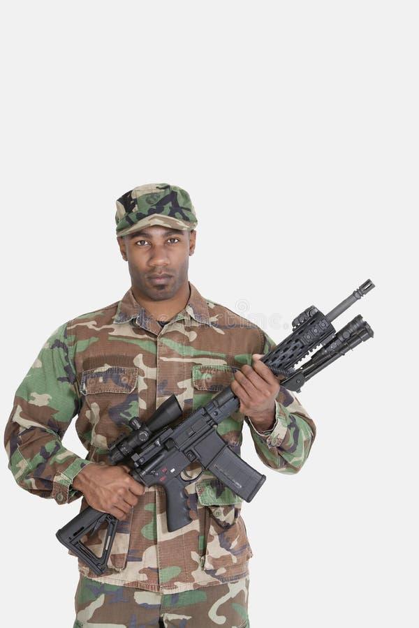 Portret van de jonge Afrikaanse Amerikaanse militair van de V.S. Marine Corps met M4 aanvalsgeweer over grijze achtergrond stock fotografie