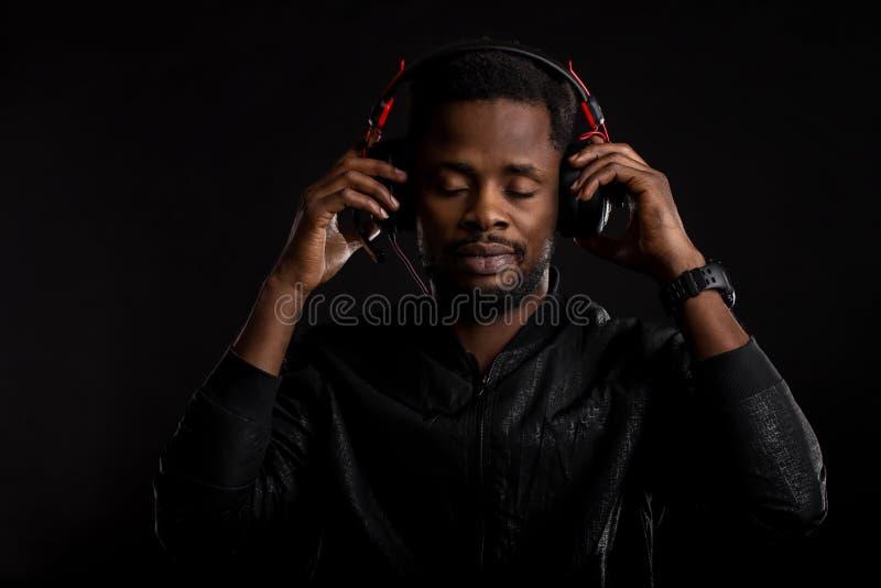 Portret van de jonge Afrikaanse mens die aan muziek met hoofdtelefoons luisteren royalty-vrije stock foto