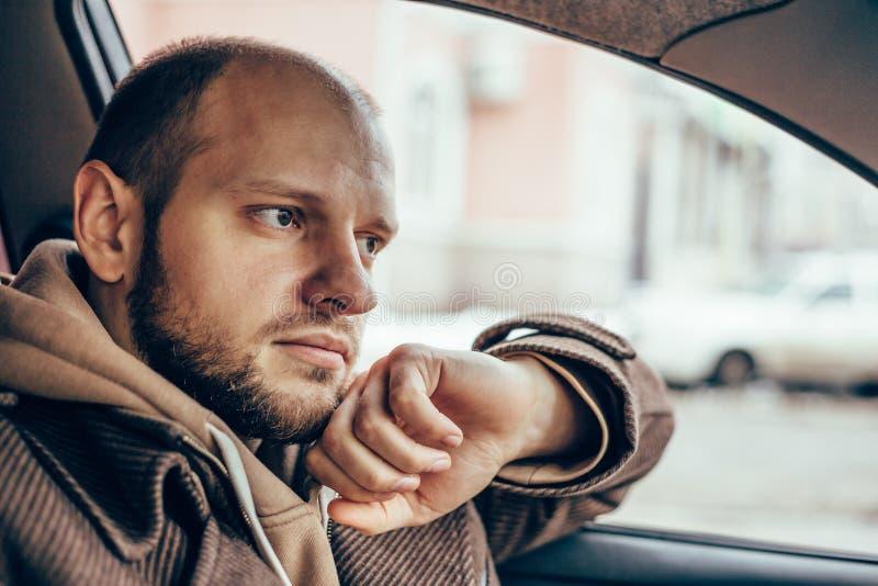 Portret van de jonge ernstige of droevige of gedeprimeerde mens die in zijn auto situeren royalty-vrije stock foto's