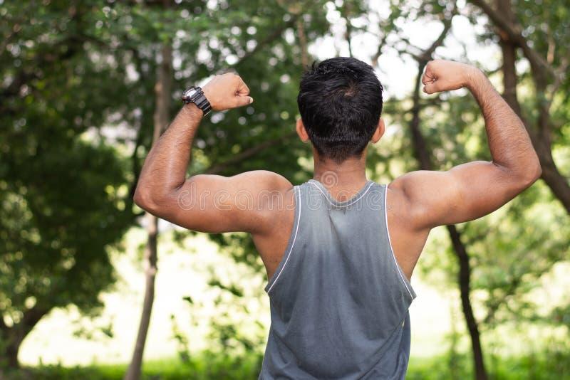 Portret van de Jonge geschikte Kaukasische mens met spierlichaam die bicepsen in openlucht op zonnige de zomerdag tonen in park stock afbeeldingen