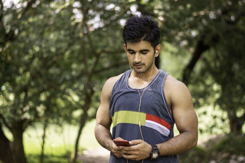 Portret van de Jonge geschikte Kaukasische mens met spierlichaam die smartphone met hoofdtelefoon in openlucht op zonnige de zome royalty-vrije stock foto