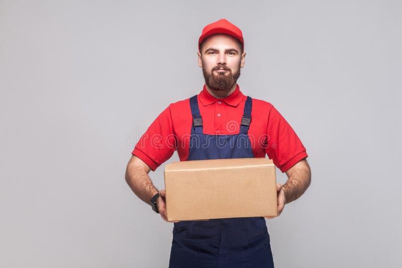 Portret van de jonge glimlachende logistische leveringsmens met baard in bl royalty-vrije stock foto's