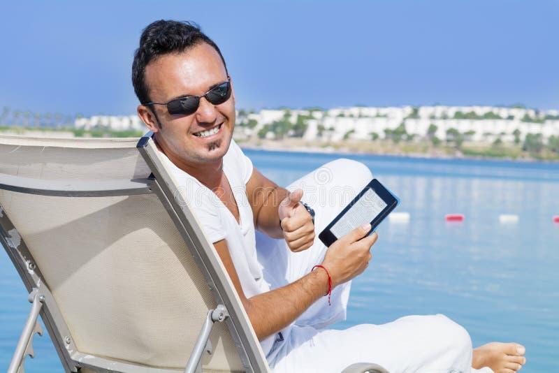 Portret van de jonge glimlachende mens met tablet in de hand op een overzees strand royalty-vrije stock afbeelding
