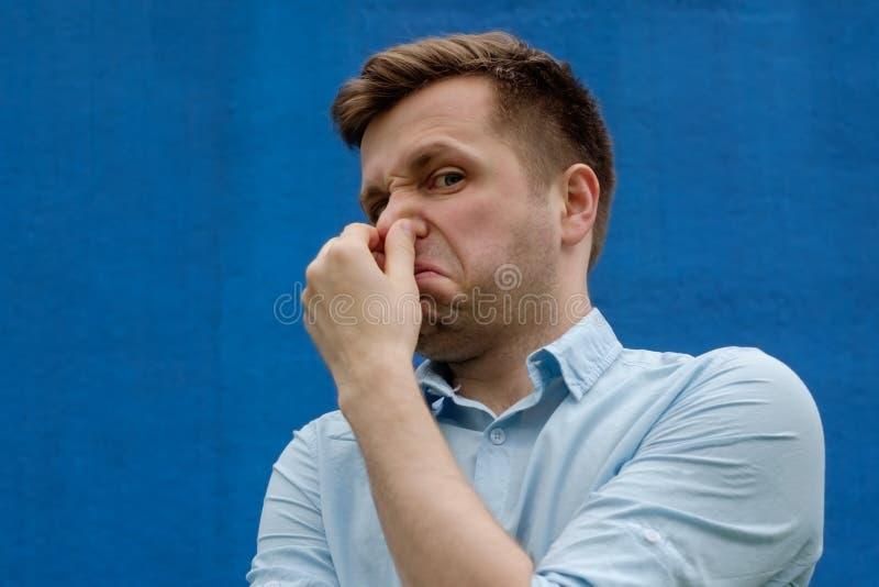 Portret van de jonge Kaukasische mens die zijn neus wegens het vreselijke ruiken sluiten royalty-vrije stock fotografie
