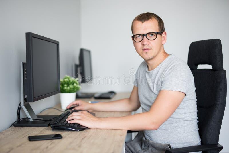 Portret van de jonge knappe mens die computer in bureau met behulp van royalty-vrije stock fotografie