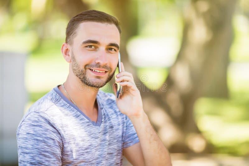 Portret van de jonge knappe jonge mens die op de celtelefoon spreken stock afbeeldingen