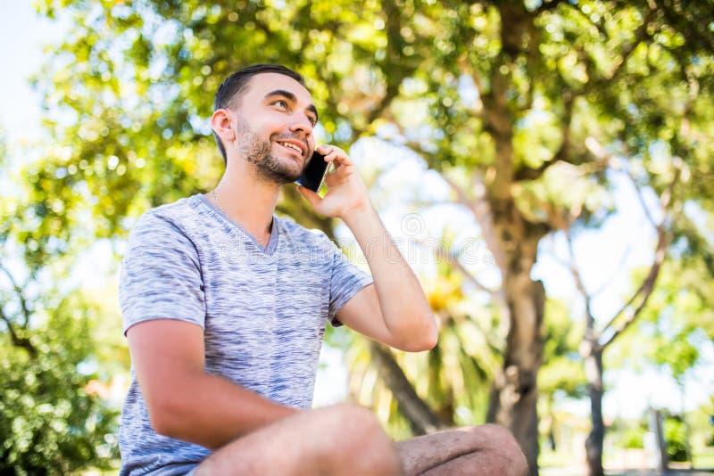 Portret van de jonge knappe jonge mens die op de celtelefoon spreken stock fotografie