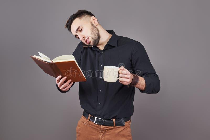 Portret van de jonge knappe mens met telefoon, kop van coffe en boek op handen Het concept overwerk, spanning en heel wat stock foto's