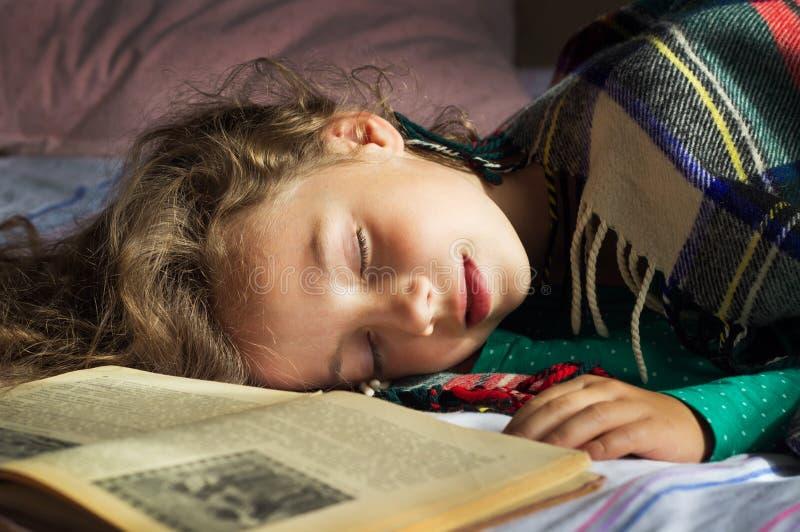 Portret van de Jonge krullende slaap van het schoolmeisje op de boeken stock fotografie