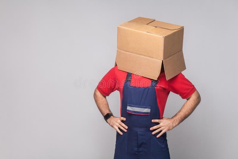 Portret van de jonge logistische leveringsmens in blauwe eenvormig en rood stock foto