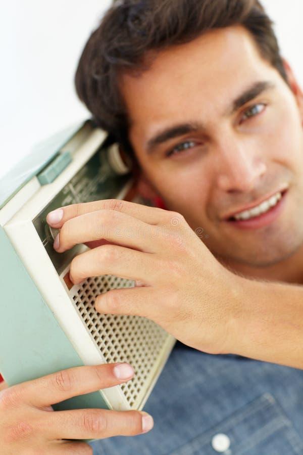 Portret van de jonge mens die aan radio luistert stock afbeelding
