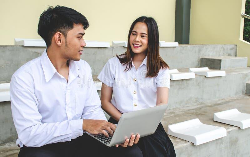 Portret van de jonge mens en meisje in universitaire eenvormige zitting en het werken aan laptop royalty-vrije stock foto