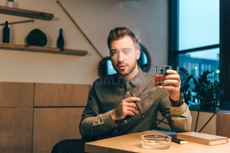 portret van de jonge mens met glas van cognac en sigaar in handen die bij lijst zitten royalty-vrije stock foto