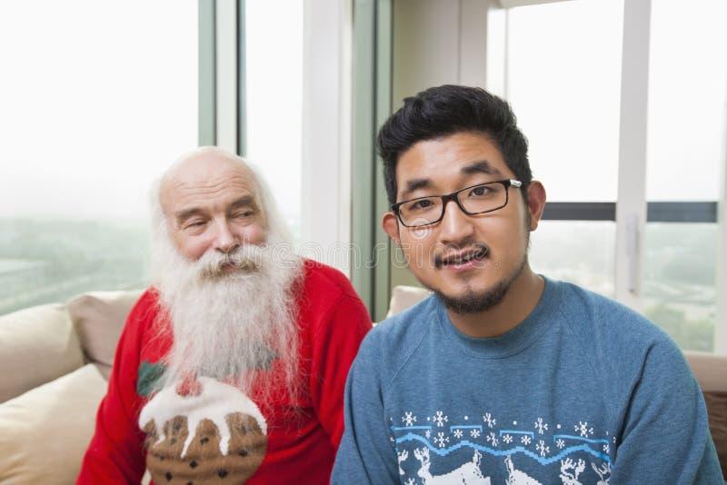 Portret van de jonge mens met grootvader die hem bekijken stock fotografie