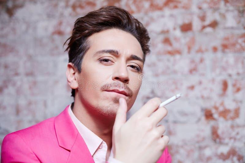 Portret van de jonge mens in roze kostuum met sigaret royalty-vrije stock foto
