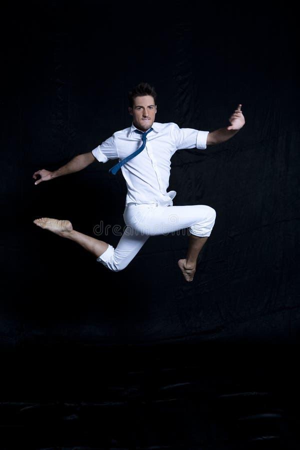 Portret van de jonge mens in wit dat elegant springt royalty-vrije stock afbeelding
