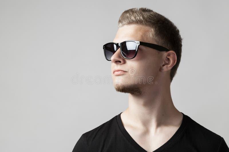 Portret van de jonge mens in zonnebril die op grijs wordt geïsoleerd royalty-vrije stock afbeelding