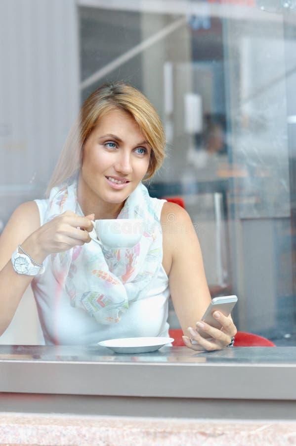 Portret van de jonge mobiele telefoon van het onderneemstergebruik terwijl het zitten in koffie stock afbeelding