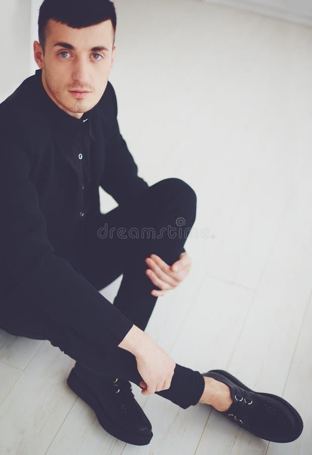 Portret van de jonge modieuze mens in donkere kleren royalty-vrije stock afbeelding