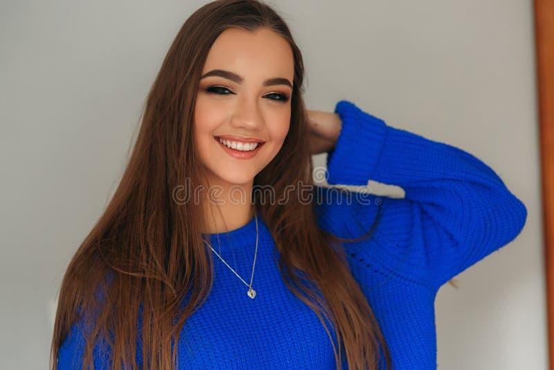 Portret van de jonge mooie glimlachende vrouw binnen Meisje in bkuesweater De Make-up van de manier stock fotografie