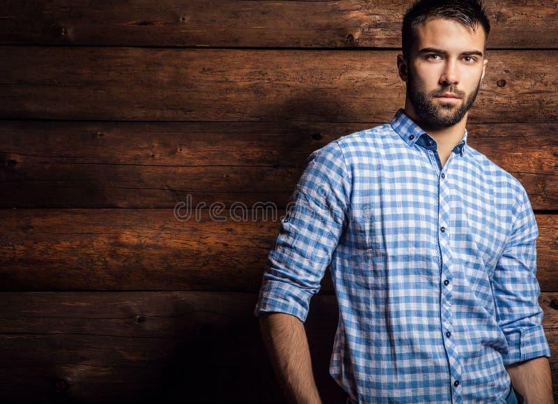 Portret van de jonge mooie modieuze mens tegen houten muur stock afbeeldingen