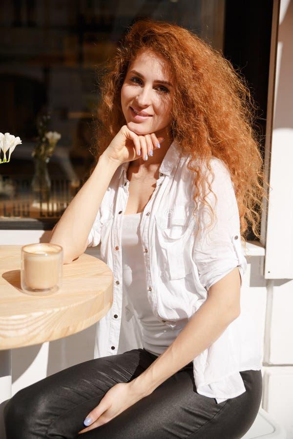 Portret van de jonge mooie zitting van de roodharigevrouw in een koffie stock afbeeldingen