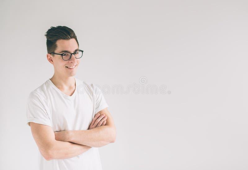 Portret van de jonge Nerd-mens glazen en t-shirt dragen die zich met gekruiste wapens bevinden en glimlachen die geïsoleerd op wi stock afbeelding