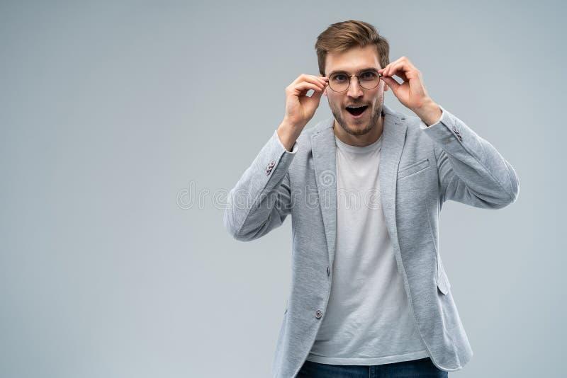 Portret van de jonge verbaasde die mens op grijze achtergrond wordt geïsoleerd stock foto's