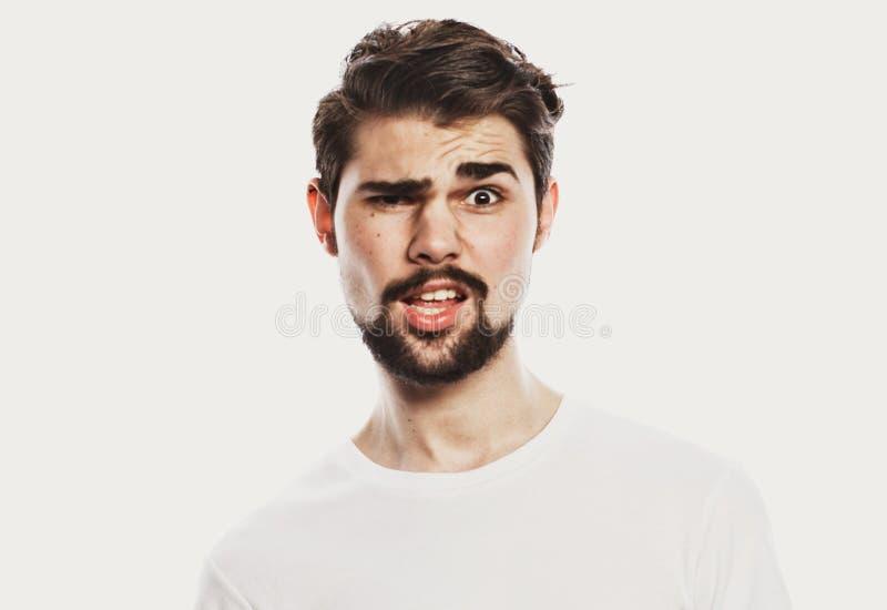 Portret van de jonge verbaasde die mens op witte achtergrond wordt geïsoleerd stock foto's