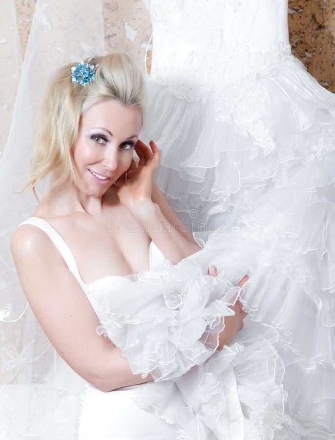 Portret van de jonge vrouw met een lang eerlijk haar dat op een witte huwelijkskleding probeert royalty-vrije stock afbeelding