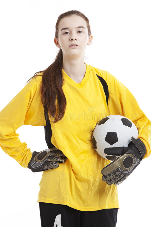 Portret van de jonge vrouwelijke bal van de voetballerholding met hand op heup tegen witte achtergrond stock fotografie