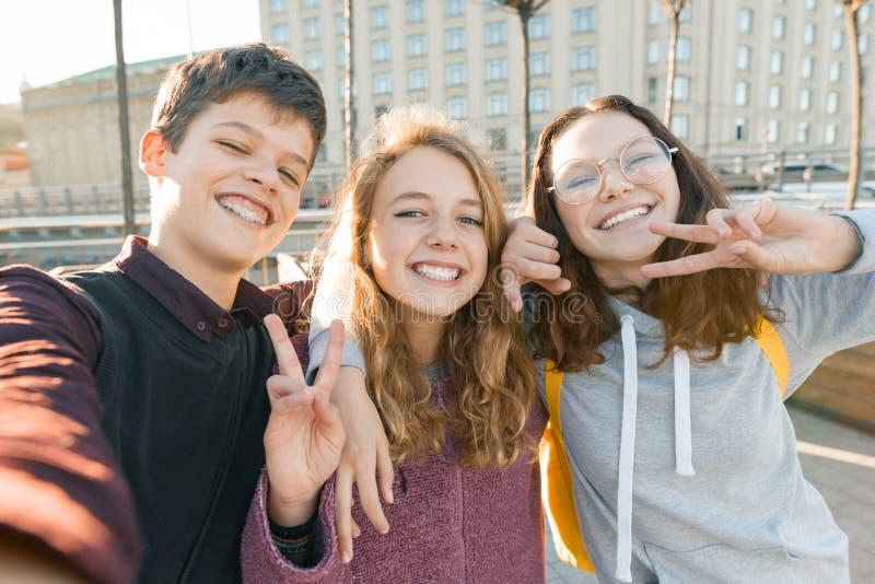 Portret van de jongen van drie tienervrienden en twee meisjes die en een selfie in openlucht glimlachen nemen Stadsachtergrond, g stock foto