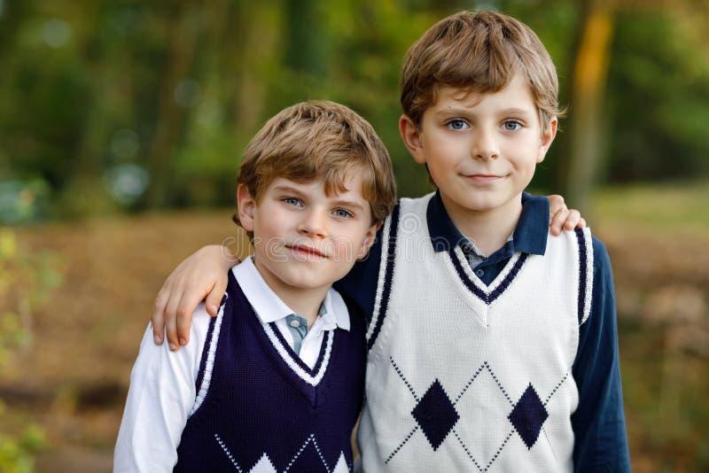 Portret van de jongens die van weinig schooljonge geitjes in bos Gelukkige kinderen, beste vrienden en siblings zitten die pret o royalty-vrije stock foto's