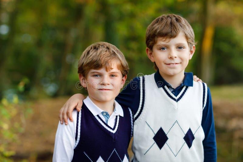 Portret van de jongens die van weinig schooljonge geitjes in bos Gelukkige kinderen, beste vrienden en siblings zitten die pret o stock foto's