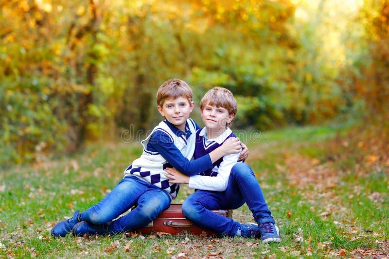 Portret van de jongens die van weinig schooljonge geitjes in bos Gelukkige kinderen, beste vrienden en siblings zitten die pret o royalty-vrije stock afbeeldingen