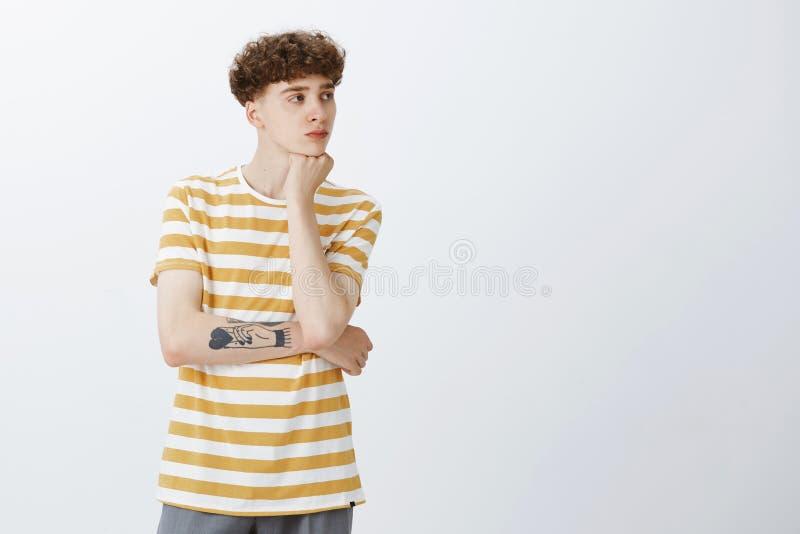 Portret van de kalme en sombere aantrekkelijke jonge mens met krullend haar en tatoegeringen die hoofd op hand leunen die net met royalty-vrije stock foto