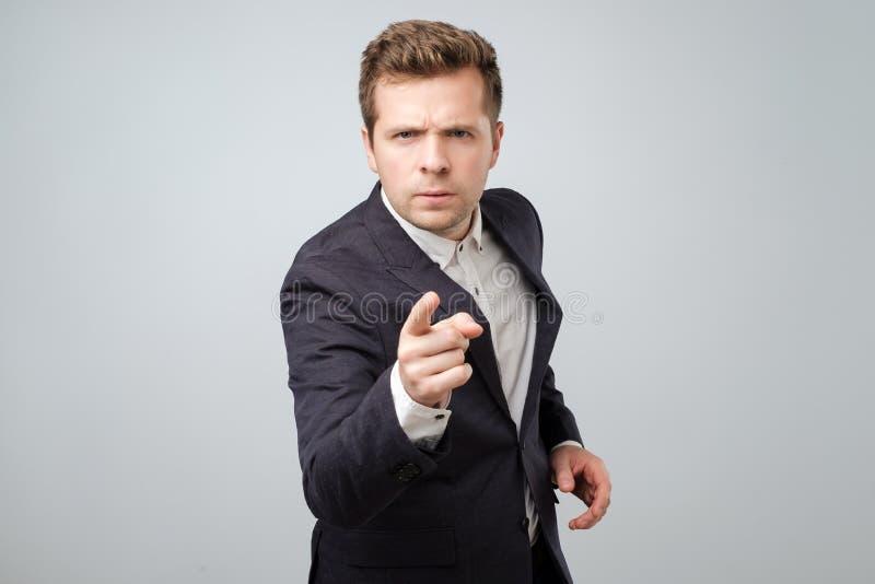 Portret van de Kaukasische boze jonge mens die in kostuum vinger richten op u stock foto