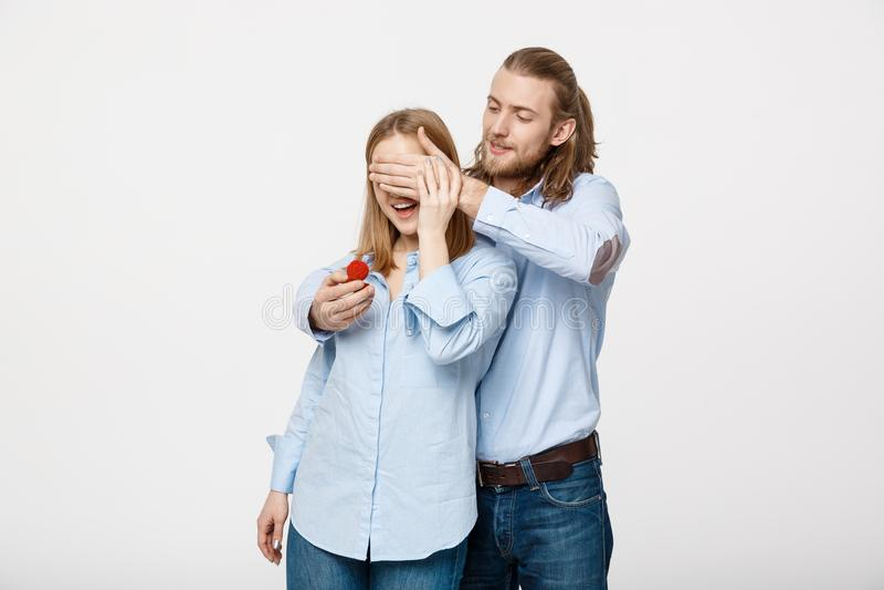 Portret van de knappe baardmens die zijn wifesogen verbergen om haar een verlovingsring voor een aanzoek aan te bieden royalty-vrije stock afbeelding