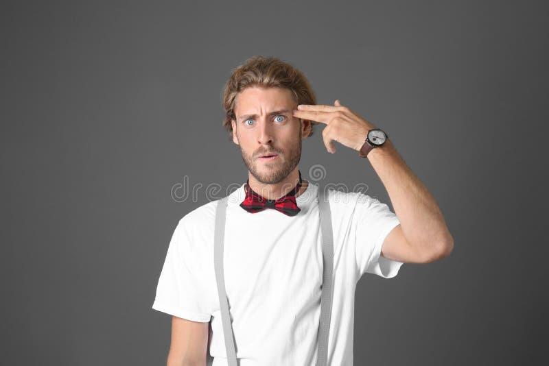 Portret van de knappe emotionele mens die het gebaar van het handpistool op grijze achtergrond tonen stock foto's