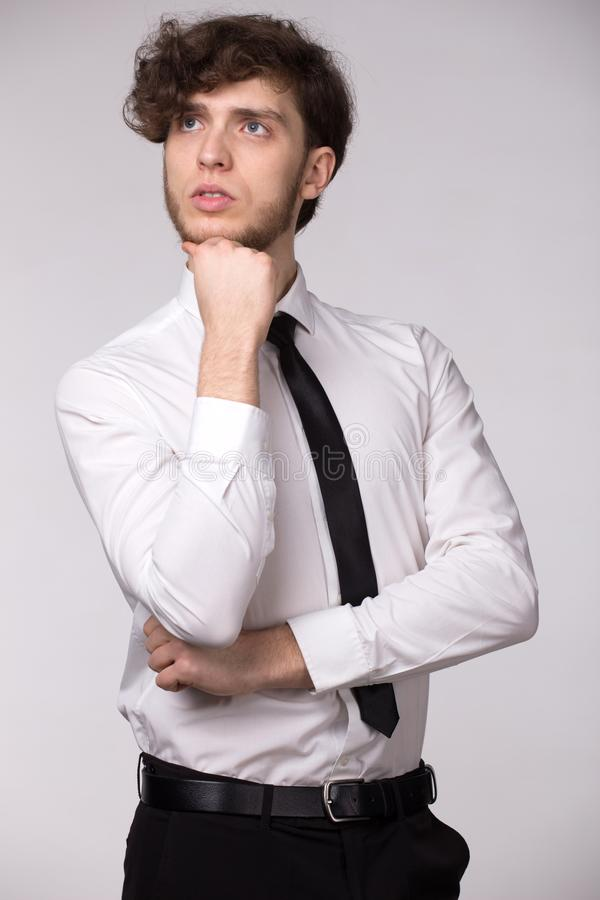 Portret van de knappe ernstige peinzende mens die in wit overhemd, naar omhoog denkend over probleem, die zijn kin houden kijken stock foto