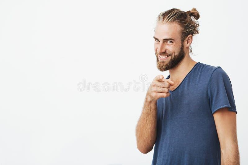 Portret van de knappe gebaarde mens met groot met wijsvinger richten in camera en brightfully kapsel die glimlachen stock fotografie