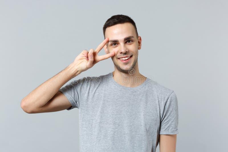 Portret van de knappe glimlachende jonge mens die in vrijetijdskleding camera die die overwinningsteken tonen kijken op grijze mu stock foto's