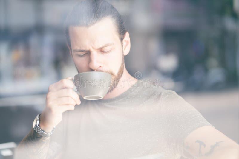 Portret van de knappe hipstermens die met baard van een kop van koffie ontspannende zitting genieten op stoel bij koffie stock afbeeldingen